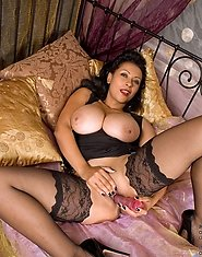 Busty Anilos Donna fucks her mature pussy with a huge dildo on the bed