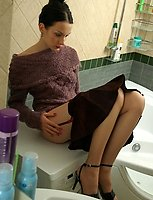 Lusty gal attaching colored garter to her suntan stockings after hot shower