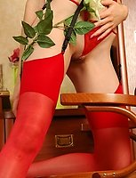 Passionate brunette mounts a table in her red stockings enjoying their feel