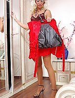 Glamour blonde peels off a trouser suit and changes her hose for stockings