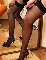 Pretty babe fitting on her plain-top stockings and garter after sweat sleep