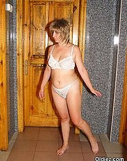 A horny mom in white lingerie poses in the toilet