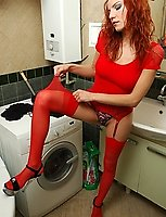 Redhead chick putting on her red stockings and garter before toying her ass