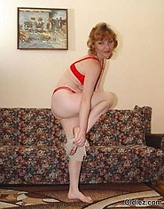 A mature woman in red lingerie poses on the couch
